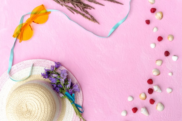 Czas na odpoczynek. kapelusz, okulary przeciwsłoneczne i narzuta na różowym tle.