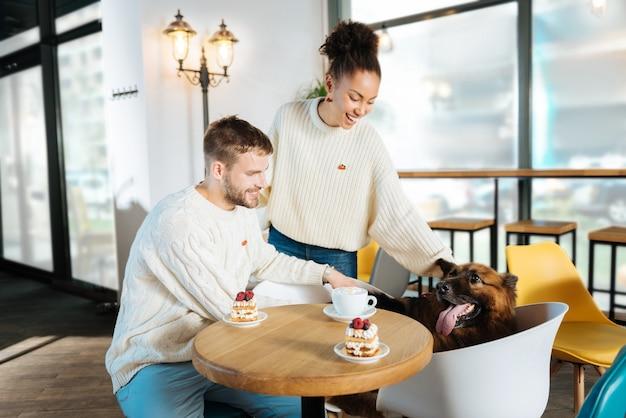 Czas na piekarnię. para nowoczesnych freelancerów czuje się zrelaksowana, przychodząc do piekarni ze swoim psem