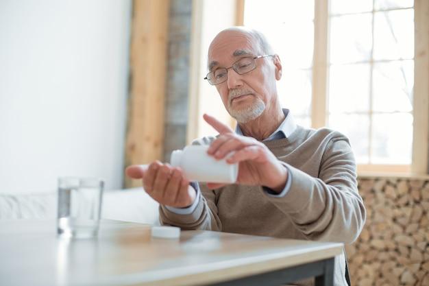Czas na pigułki. poważny, przyjemny starszy mężczyzna siedzi przy stole, podczas gdy wkłada tabletki do ręki i patrzy w dół