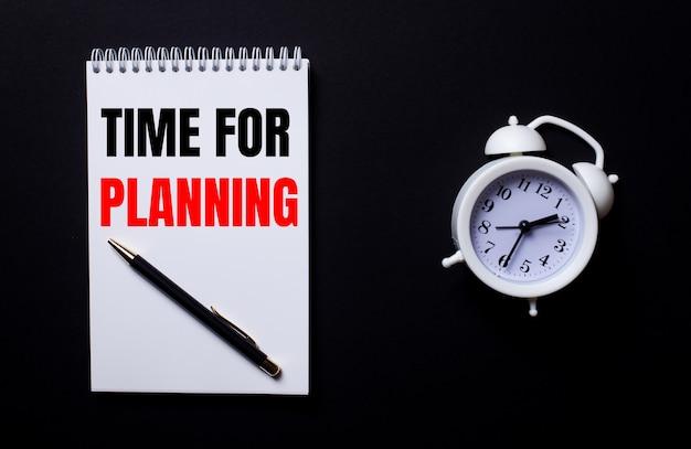 Czas na planowanie jest zapisany w białym notesie obok białego budzika na czarnej powierzchni