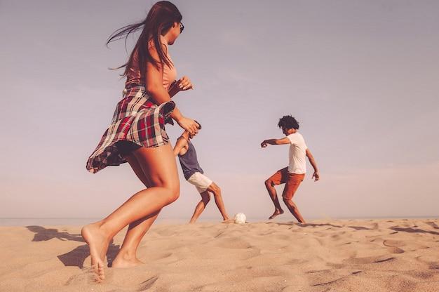 Czas na plażę. trzech wesołych młodych ludzi bawiących się piłką nożną na plaży