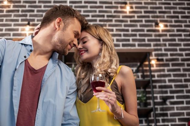 Czas na pocałunek. blondwłosa piękna, rozpromieniona kobieta uśmiecha się, całując swojego przystojnego troskliwego męża