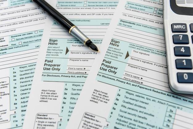 Czas na podatki, formularz federalny z długopisem i kalkulatorem, biurko. papierkowa robota
