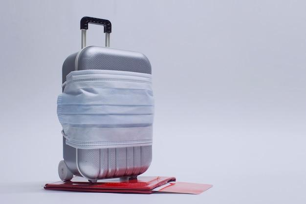 Czas na podróż. koncepcja bezpiecznego wypoczynku podczas pandemii koronawirusa covid-19. walizka podróżna z maską medyczną i biletami lotniczymi z paszportem.