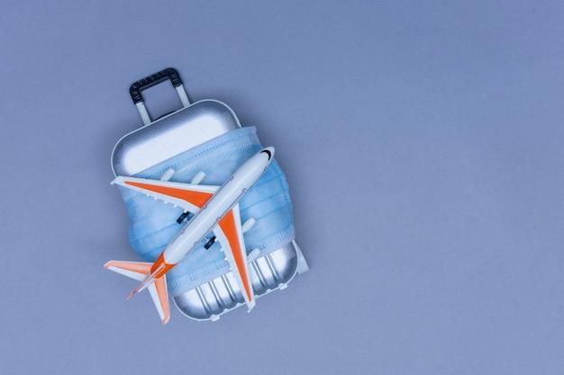 Czas na podróż. koncepcja bezpiecznego wypoczynku podczas pandemii koronawirusa covid-19. walizka podróżna z maską medyczną i samolotem.