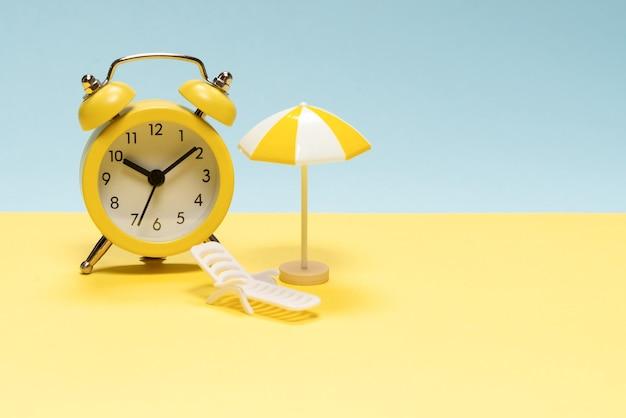 Czas na podróż. leżak, żółty parasol i budzik na żółtym, niebieskim tle.