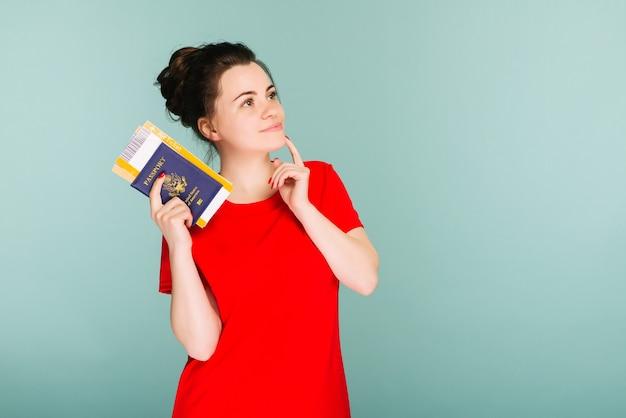 Czas na podróż. nowoczesna modna uśmiechnięta kobieta w czerwonej sukience z biletami lotniczymi i paszportem w dłoni.