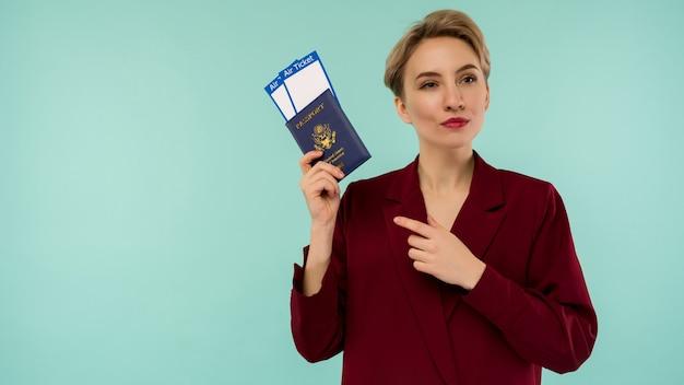 Czas na podróż. nowoczesna modna uśmiechnięta kobieta w czerwonym garniturze, wskazująca na bilety lotnicze i paszport w dłoni.