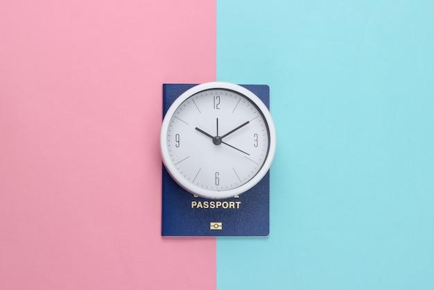 Czas na podróż. paszport i zegar na różowym niebieskim tle pastelowych. widok z góry