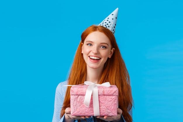 Czas na prezent. wesoła rudowłosa nastolatka, uczennica obchodząca urodziny, trzymająca uroczy różowy owinięty prezent i ubrana w czapkę b-day, radośnie uśmiechnięta stojąca na niebieskim tle