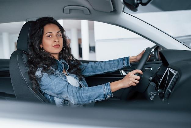 Czas na przejażdżkę. śliczna dziewczyna z czarnymi włosami próbuje swojego nowego drogiego samochodu w salonie samochodowym