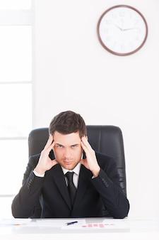 Czas na przerwę. przygnębiony młody człowiek w formalwear patrząc na kamerę i trzymając głowę w dłoniach siedząc w swoim miejscu pracy z zegarem ściennym w tle