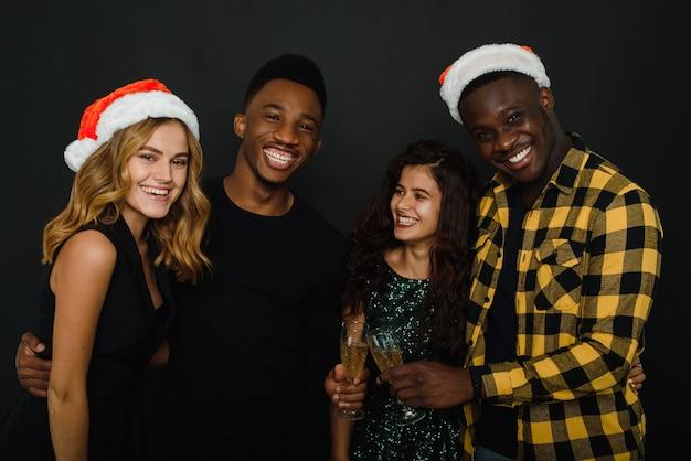 Czas na przyjęcie świąteczne. do pasa czterech przyjaciół w czapkach mikołaja, którzy bawią się i piją szampana podczas przyjęcia sylwestrowego, na białym tle na czarnym tle.