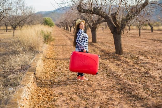 Czas na relaks, podróż i wakacje koncepcja - młoda kobieta z czerwoną walizką w przyrodzie lato