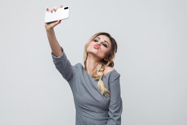 Czas na samojebkę! autoportret szczęśliwego pięknego nastolatka blogera ubranego w szarą sukienkę z warkoczem na głowie stojącego, wysyłającego pocałunek powietrzny i robiący selfie. wewnątrz, na białym tle, studio strzał, szare tło