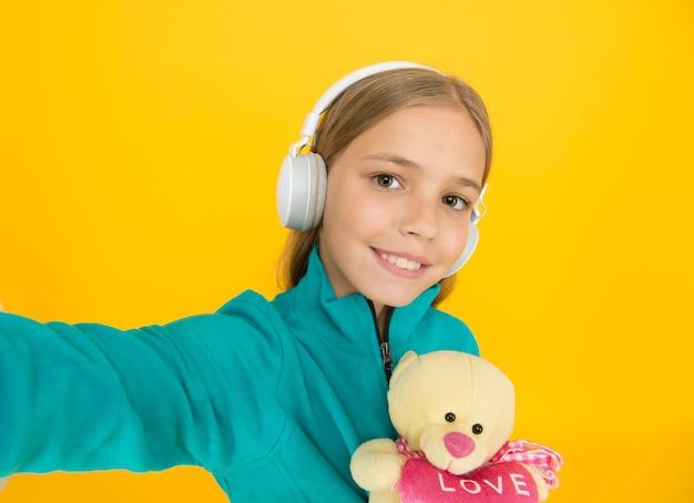 Czas na samojebkę. edukacja muzyczna. gust muzyczny. akcesoria muzyczne. wypoczynek i zabawa. mam to uczucie. dziewczyna z miękkimi zabawkami słuchania muzyki bezprzewodowymi słuchawkami. zakochany w dźwięku stereo.