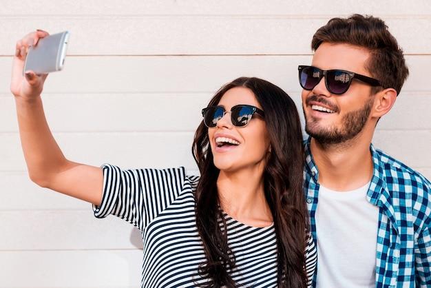Czas na samojebkę. piękna młoda kochająca para robi selfie na smartfonie stojąc na zewnątrz