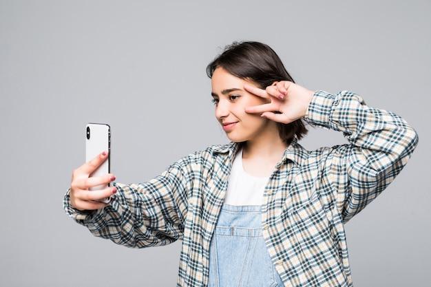 Czas na samojebkę. radosne młode kobiety dokonywanie selfie jej inteligentny telefon na białym tle