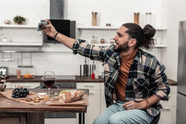 Czas na samojebkę. radosny brunetka mężczyzna patrzący w kamerę smartfona podczas robienia zdjęć