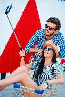 Czas na samojebkę! widok z góry szczęśliwej młodej pary kochającej robienia selfie na smartfonie podczas wspólnej zabawy na świeżym powietrzu