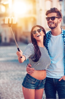 Czas na selfie. radosna młoda kochająca para robi selfie na smartfonie stojąc na zewnątrz