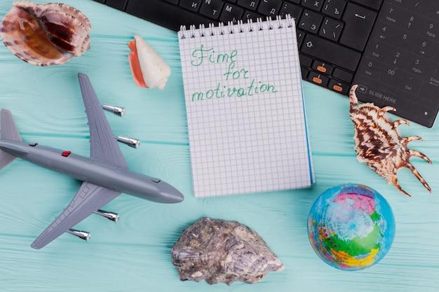 Czas na słowa motywacyjne na notebooku w kompozycji podróżnej. samolot, kula ziemska, muszle na niebieskim biurku.
