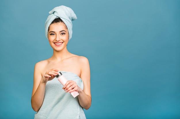 Czas na spa! portret uśmiechnięta piękna kobieta w ręcznik na ciele i na głowie trzymając balsam do ciała na białym tle na niebieskim tle.