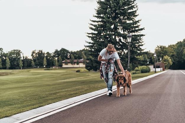 Czas na spacer. pełna długość przystojnego młodego mężczyzny spacerującego z psem podczas spędzania czasu na świeżym powietrzu