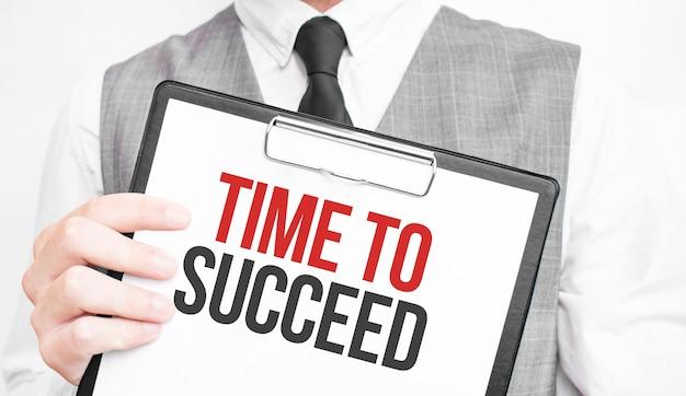 Czas na sukces napis na notatniku w rękach biznesmena na szarym tle, mężczyzna wskazuje palcem na tekst