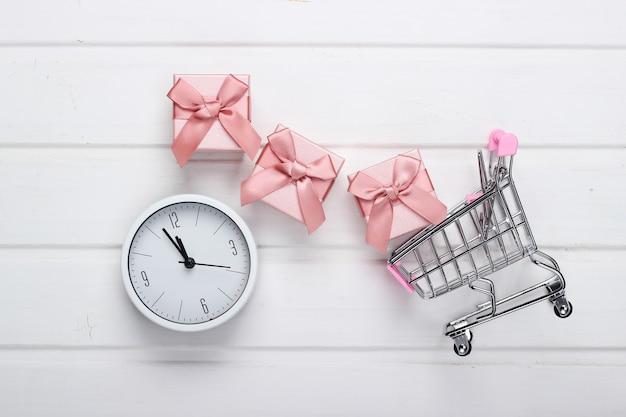 Czas na świąteczne zakupy. wózki do supermarketów z pudełkami na prezenty, zegar na białej powierzchni drewnianej. minimalizm. widok z góry