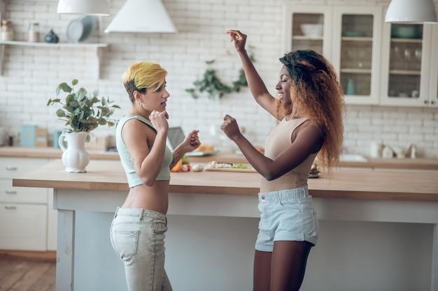 Czas na taniec. dwie młode dziewczyny szczupłe dorosłych w ubranie, taniec w kuchni po południu w dobrym nastroju