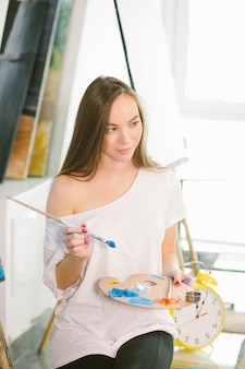 Czas na tworzenie. atrakcyjna kobieta pozuje fullface podczas malowania głąbika morza