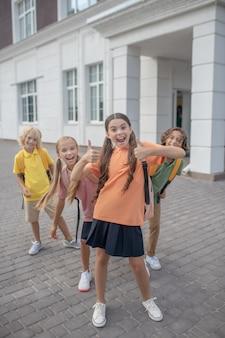 Czas na zabawę. dzieci w wieku szkolnym bawiące się na szkolnym podwórku i czujące się radośnie
