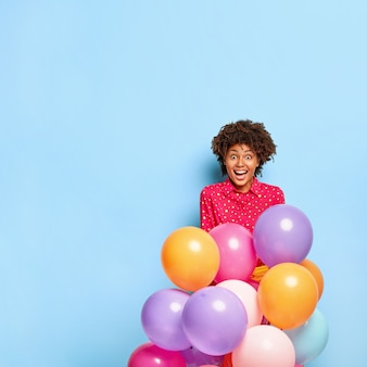 Czas na zabawę. nadzwyczajna szczęśliwa african american kobieta cieszy się przyjęciem, trzyma kolorowe balony z helem