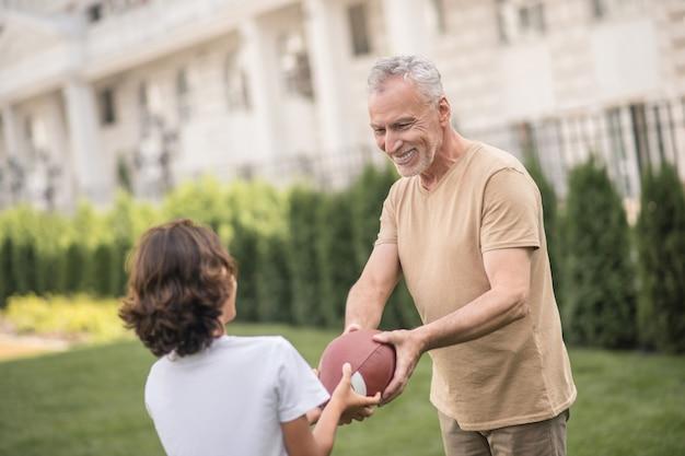 Czas na zabawę. siwowłosy tata daje synowi piłkę i uśmiecha się