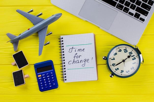 Czas na zmianę koncepcji płaskiej. budzik z samolocikiem i kalkulatorem na żółtym drewnie.