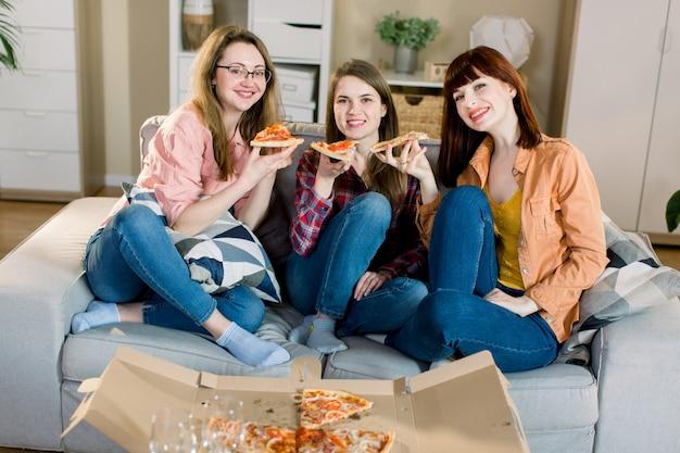 Czas pizzy. trzy całkiem uśmiechnięte kobiety jedzące pizzę, wspólnie bawiące się w domowej jadalni. pojęcie przyjaźni, jedzenia, stylu życia