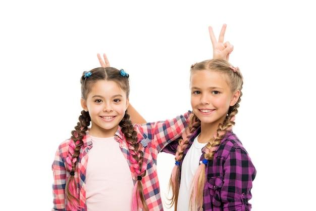 Czas płynie szybko, gdy dobrze się bawisz. szczęśliwe dzieci bawią się razem. małe dziewczynki robią sobie rogi dla zabawy. śmieszni przyjaciele na białym tle. zabawa i gry. dzieciństwo.