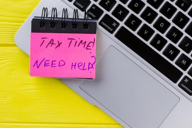 Czas podatkowy potrzebuje pomocy. laptop pc na żółtym widoku z góry.