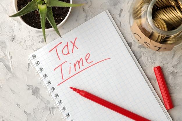 Czas podatkowy słowo w zeszycie ze słoikiem monet i kwiatem na jasnym betonowym tle. widok z góry