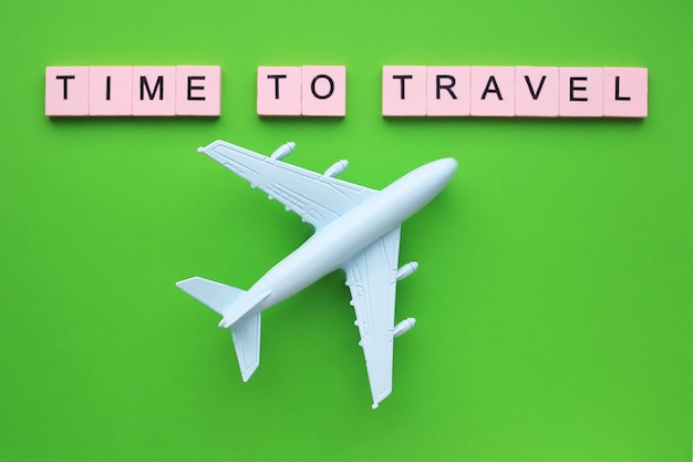 Czas podróżować słowo w różowych blokach i zabawkowy samolot na zielonej powierzchni