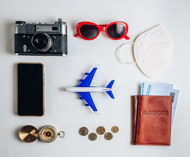 Czas podróży koncepcja, aparat fotograficzny, paszport, pieniądze, telefon z pustym ekranem, okulary przeciwsłoneczne i kompas na białym tle. planowanie wakacji. płaski układanie, widok z góry