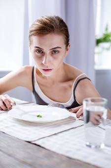 Czas posiłku. smutna blada kobieta siedząca przy stole podczas jedzenia posiłku