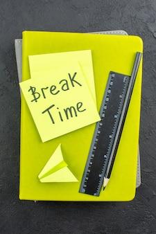 Czas przerwy w widoku z góry napisany na karteczkach samoprzylepnych linijka czarny ołówek na zeszytach na ciemnej ścianie