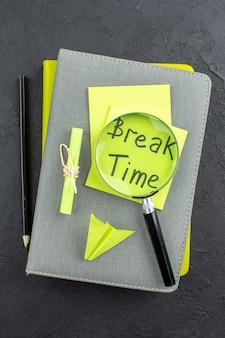 Czas przerwy w widoku z góry napisany na żółtych karteczkach samoprzylepnych lupa czarny ołówek na notatnikach na ciemnym stole