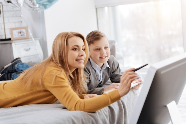 Czas razem. miły szczęśliwy zachwycony chłopiec leżąc na łóżku razem z matką i uśmiechając się, patrząc na monitor