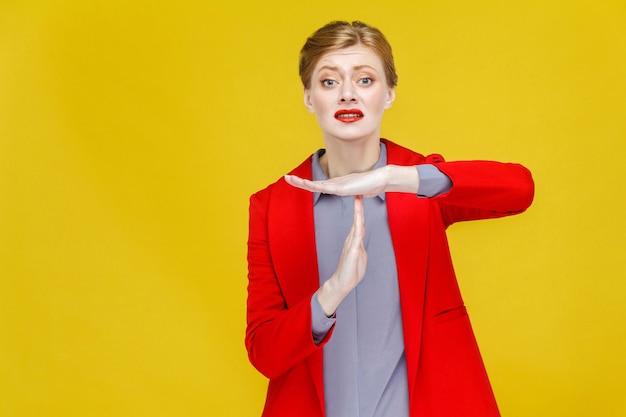 Czas się nieszczęśliwa biznesowa kobieta w czerwonym garniturze pokazując znak pauzy