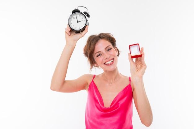 Czas się ożenić, dziewczyna zgłasza dobre wieści dla pana młodego, portret panny młodej z budzikiem i obrączką w dłoniach