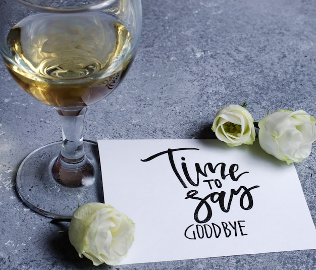 Czas się pożegnać. napis na białej kartce papieru. białe wino w szklance. pojęcie - pogorszenie relacji między ludźmi