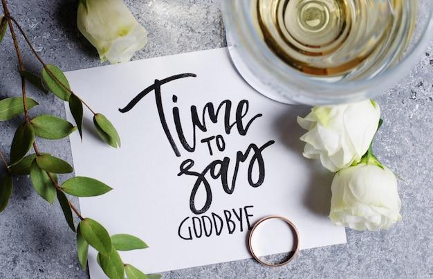Czas się pożegnać. napis na białej kartce papieru. białe wino w szklance. złoty pierścionek zaręczynowy. pojęcie - pogorszenie relacji między ludźmi